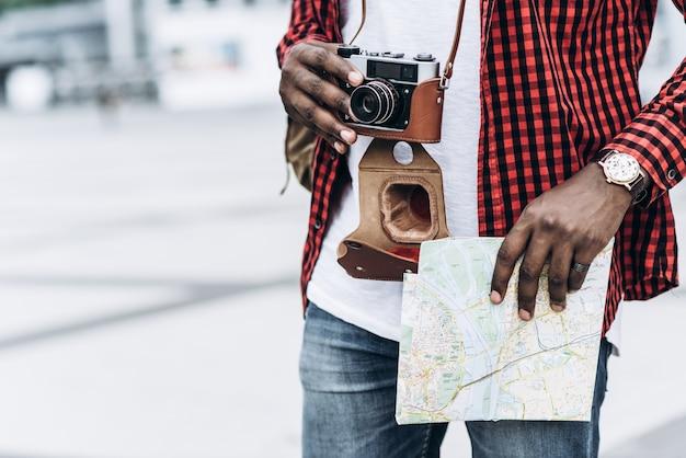 Beau et heureux touriste afro-américain avec vieille caméra et carte dans la ville moderne
