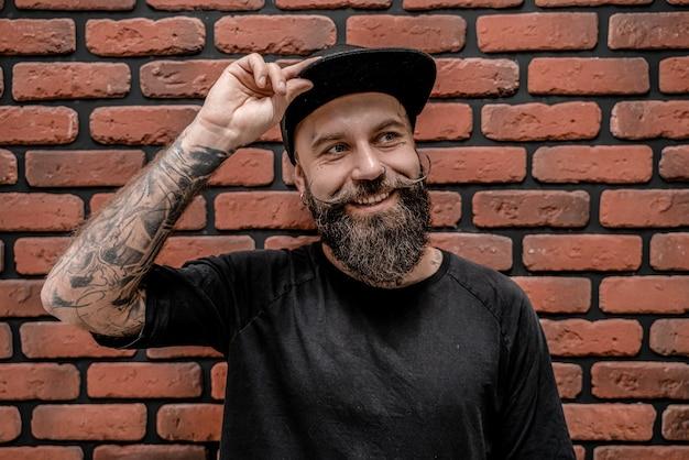 Beau hipster à l'ancienne en t-shirt et casquette, a l'air heureux et sourit. sur un fond de brique.