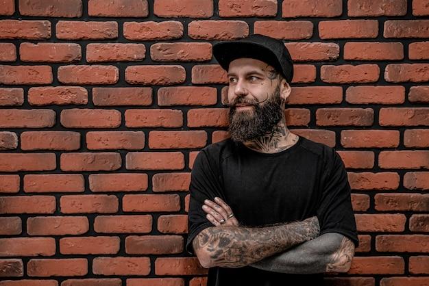 Beau hipster à l'ancienne en t-shirt et casquette, pose avec les bras croisés. isolé sur un fond de brique.