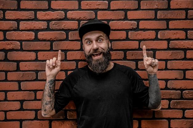 Beau hipster à l'ancienne en t-shirt et casquette, pose drôle et sourire. sur un fond de brique.