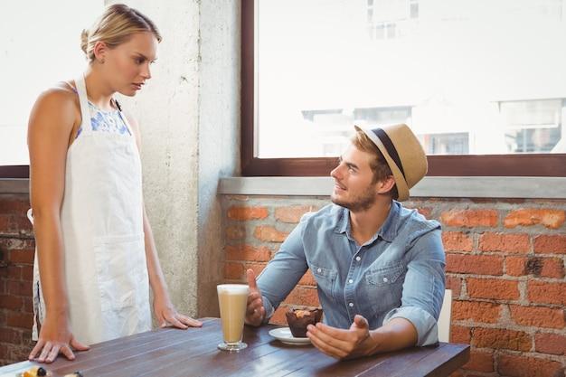 Beau hipster parlant à une serveuse blonde