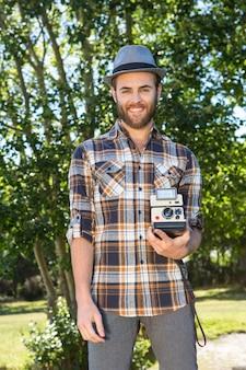 Beau hipster en utilisant un appareil photo vintage