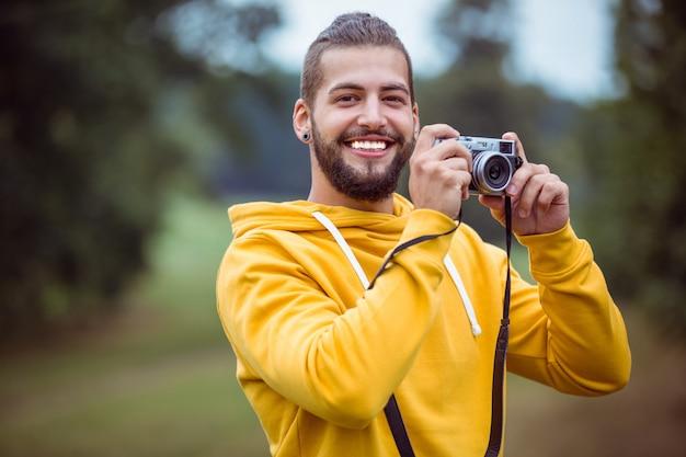 Beau hipster utilisant un appareil photo vintage