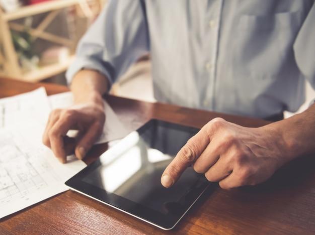 Beau homme d'affaires mature à l'aide d'une tablette numérique