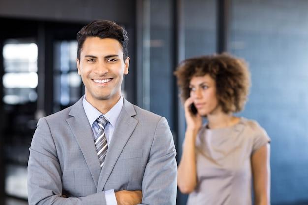 Beau homme d'affaires posant pendant que son collègue parle au téléphone