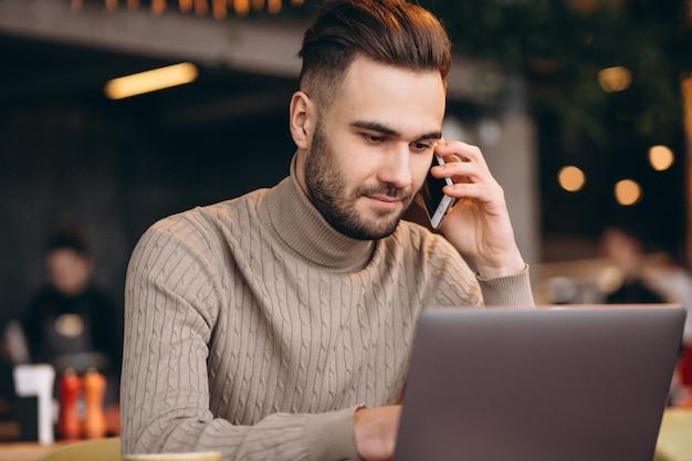Beau homme d'affaires travaillant sur ordinateur et boire du café dans un café