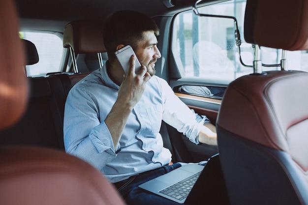 Beau homme d'affaires travaillant sur un ordinateur en voiture