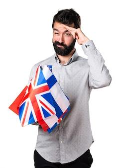 Beau homme à la barbe tenant de nombreux drapeaux et saluant