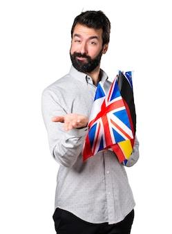 Beau homme à la barbe tenant de nombreux drapeaux et tenant quelque chose