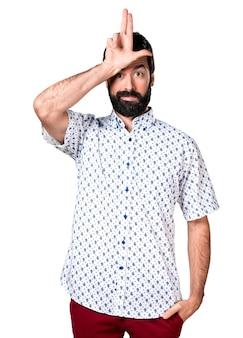 Beau homme brune à la barbe faisant signe stupide