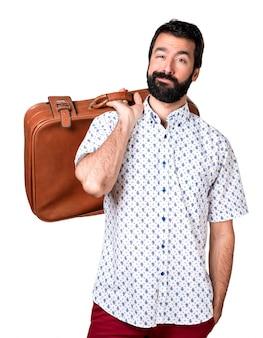 Beau homme brune à la barbe tenant une mallette vintage