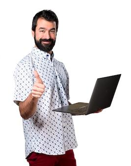 Beau homme marron avec barbe avec ordinateur portable