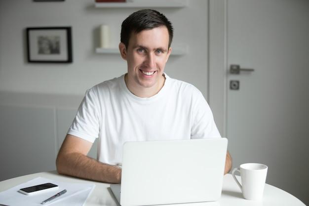 Beau homme souriant au bureau blanc travaillant avec un ordinateur portable
