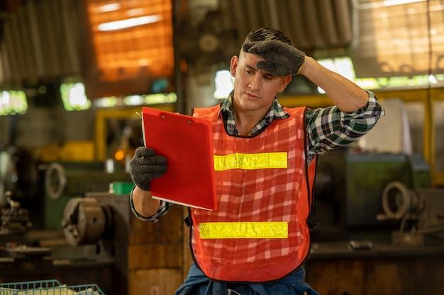 Beau ingénieur portant l'uniforme travaillant en vérifiant le stock d'usine sur les machines