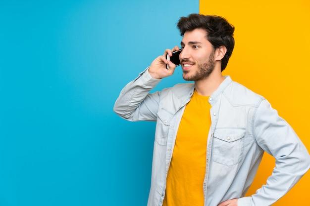 Beau sur isolé coloré en gardant une conversation avec le téléphone mobile