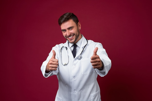 Beau jeune adulte médecin caucasien sur fond rouge montrant des vignettes