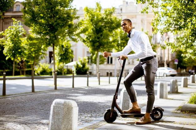 Beau jeune afro-américain à l'aide d'un scooter électrique dans la rue