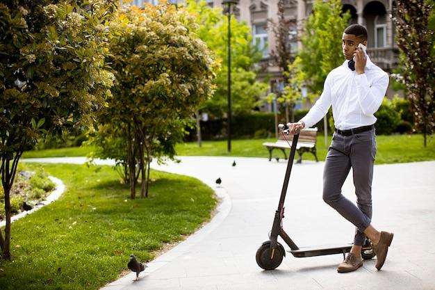 Beau jeune afro-américain à l'aide de téléphone mobile en se tenant debout par scooter électrique dans une rue