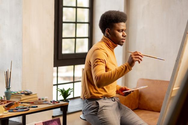 Beau jeune artiste assis devant la toile tout en créant une nouvelle image
