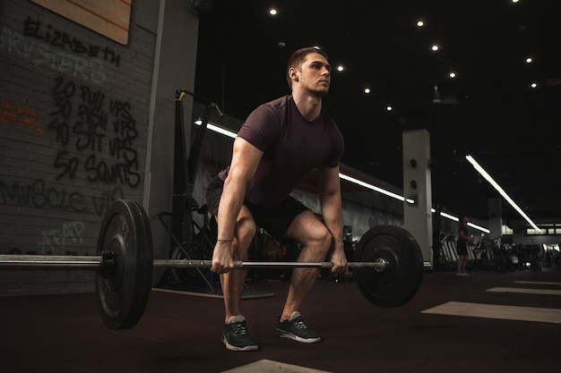 Beau jeune athlète masculin faisant des exercices de soulevé de terre au gymnase d'entraînement fonctionnel