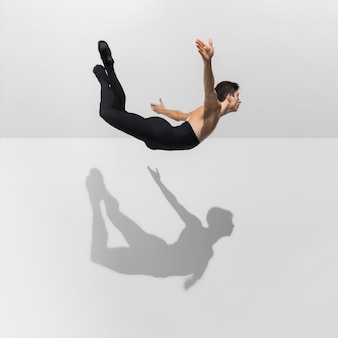 Beau jeune athlète masculin pratiquant sur blanc avec des ombres en saut, vol aérien