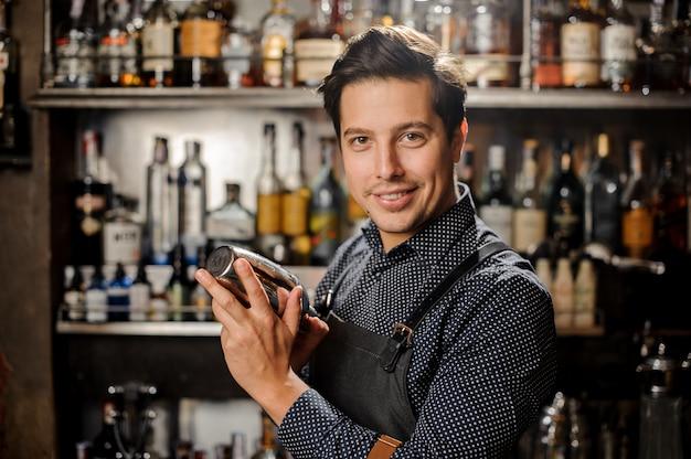 Beau et jeune barman aux cheveux bruns souriant avec un shaker