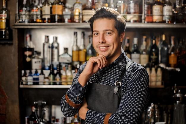 Beau et jeune barman aux cheveux bruns souriant