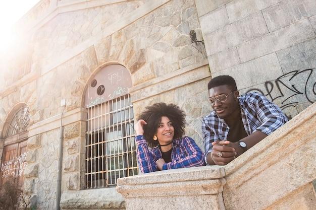 Beau jeune beau couple de race africaine noire gaie profitant de l'activité de loisirs dans la ville en milieu urbain avec des bâtiments anciens. amusez-vous et appréciez en amitié. journée ensoleillée d'été