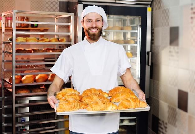 Un beau jeune boulanger tient un plateau avec des croissants devant une boulangerie et sourit.