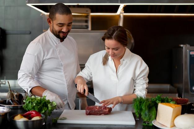 Beau jeune chef africain cuisine avec sa petite amie de race blanche dans la cuisine un cuisinier apprend à une fille à cuisiner. homme et femme cuisinant dans une cuisine professionnelle. relation interraciale