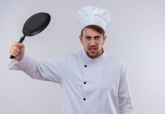 Un beau jeune chef barbu furieux homme vêtu d'un uniforme de cuisinière blanc et chapeau attaquant avec poêle sur un mur blanc