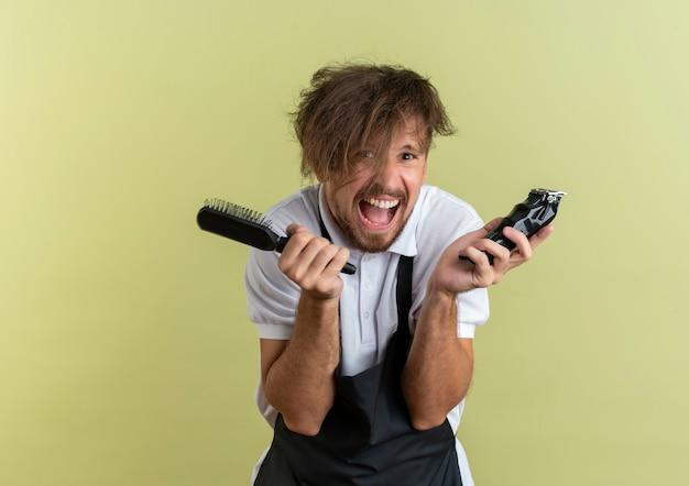 Beau jeune coiffeur aux cheveux sauvages tenant une tondeuse à cheveux isolé sur fond vert olive avec espace copie