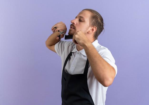 Beau jeune coiffeur portant l'uniforme de peignage et de couper sa propre barbe isolé sur fond violet avec copie espace
