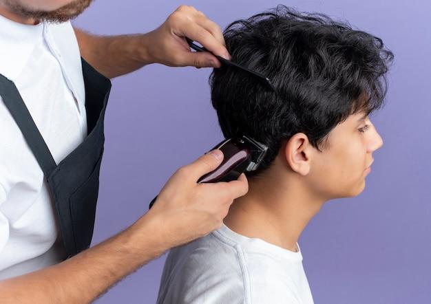 Beau jeune coiffeur en uniforme faisant la coupe de cheveux pour jeune client isolé sur fond violet