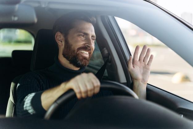 Beau jeune conducteur souriant de voiture agitant la main en signe de salutation en conduisant la voiture avec des émotions de plaisir. notion de transport