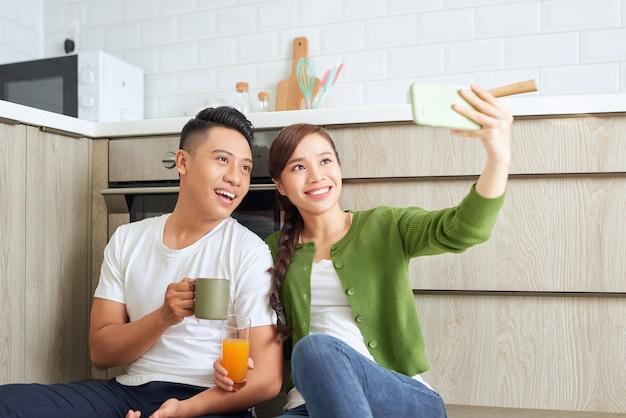 Beau jeune couple amoureux assis sur le sol de la cuisine, prenant des selfies à l'aide d'un téléphone intelligent,