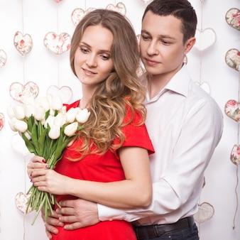 Beau jeune couple amoureux d'un bouquet de fleurs