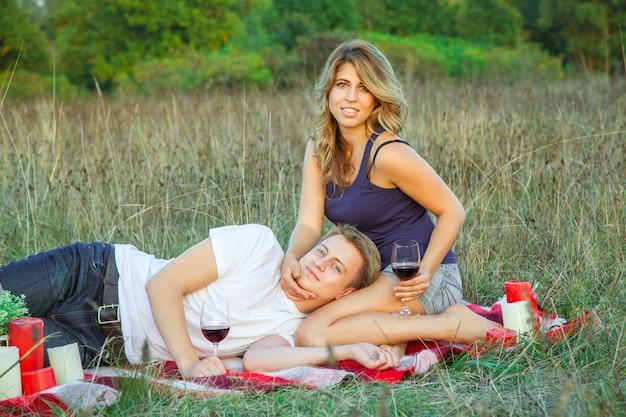 Beau jeune couple d'amoureux heureux en pique-nique allongé sur un plaid dans le champ par une journée d'été ensoleillée en profitant, en tenant et en buvant du vin et en se reposant. regardant la caméra et souriant.