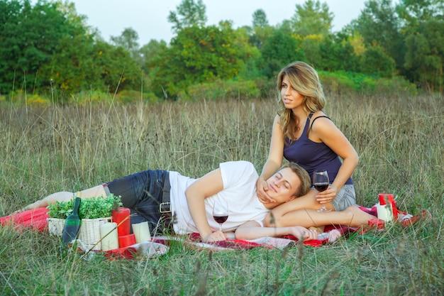 Beau jeune couple d'amoureux heureux en pique-nique allongé sur un plaid dans le champ par une journée d'été ensoleillée en profitant, en tenant et en buvant du vin et en se reposant.