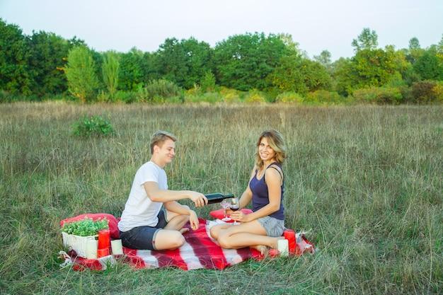 Beau jeune couple d'amoureux heureux en pique-nique allongé sur un plaid dans le champ par une journée d'été ensoleillée, profitant, tenant du vin et se reposant. regardant la caméra et souriant.