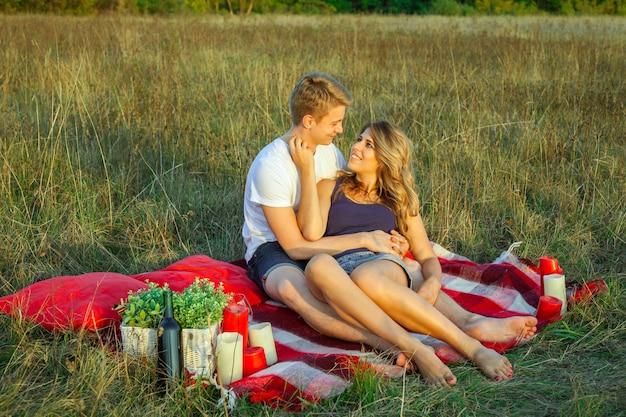 Beau jeune couple d'amoureux heureux en pique-nique allongé sur un plaid le jour d'été ensoleillé, profitant et se reposant. étreignant et se regardant et souriant.
