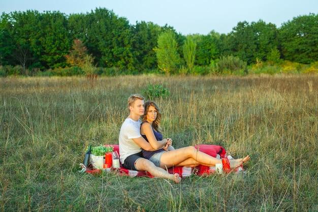 Beau jeune couple d'amoureux heureux en pique-nique allongé sur un plaid le jour d'été ensoleillé, profitant et se reposant. étreindre et regarder vers la nature.