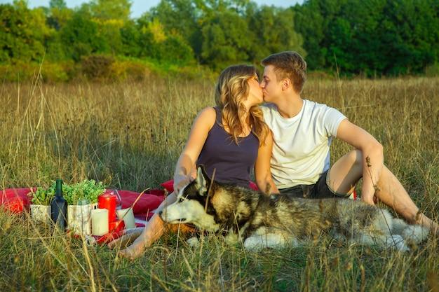 Beau jeune couple d'amoureux heureux en pique-nique allongé sur un plaid avec leur chien dans le champ par une journée d'été ensoleillée, profitant et se reposant. embrasser et amusez-vous.