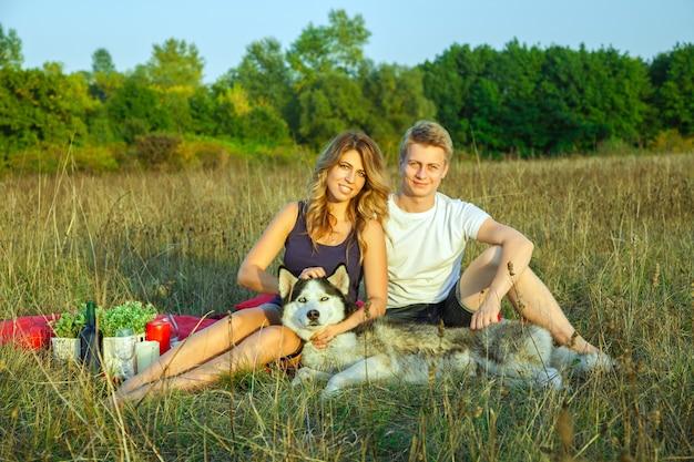 Beau jeune couple d'amoureux heureux en pique-nique allongé sur un plaid avec leur chien dans le champ par une journée d'été ensoleillée, profitant et se reposant. regardant la caméra et souriant.