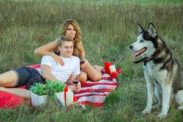 Beau jeune couple d'amoureux heureux en pique-nique allongé sur un plaid avec son chien dans le champ par une journée d'été ensoleillée en profitant, en tenant et en buvant du vin et en se reposant. regardant leur chien et souriant.