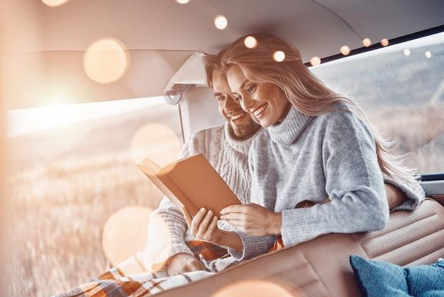 Beau jeune couple d'amoureux lisant un livre ensemble et souriant tout en passant du temps dans leur minibus