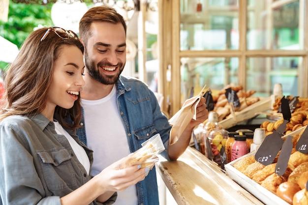 Beau jeune couple amoureux marchant dehors dans la rue de la ville, faisant l'épicerie