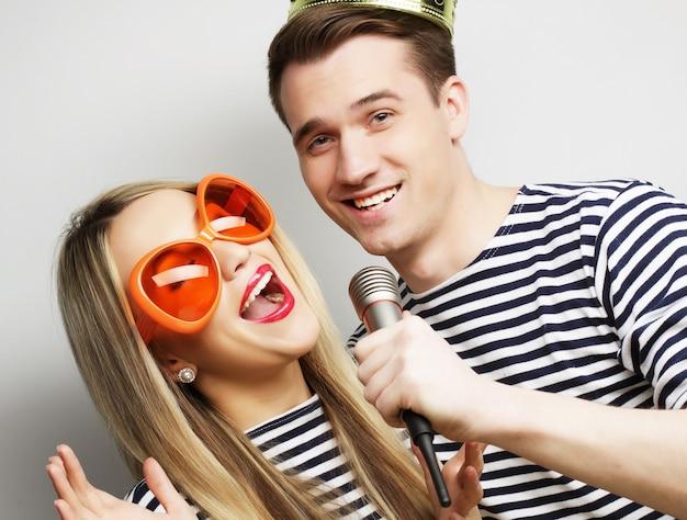Beau jeune couple d'amoureux avec microphone