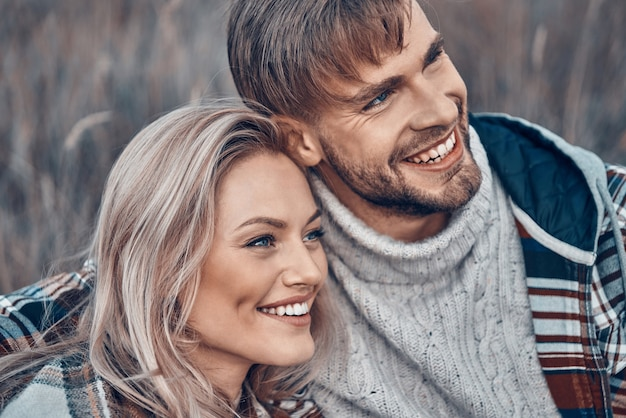 Beau jeune couple d'amoureux se liant et souriant tout en passant du temps à l'extérieur