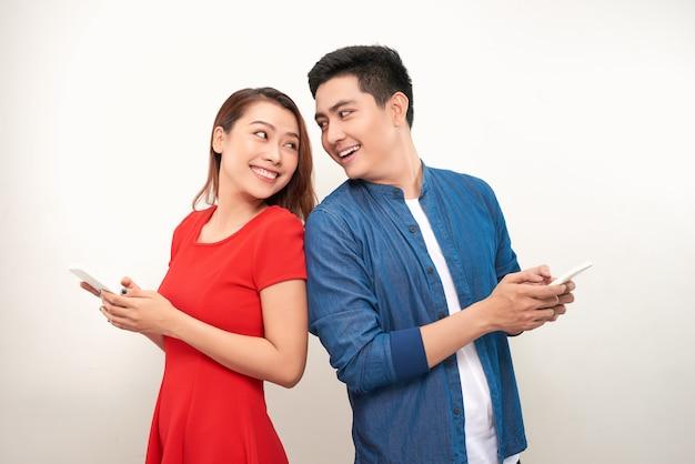 Beau jeune couple asiatique en vêtements décontractés utilise des smartphones, regarde la caméra et sourit, debout dos à dos sur fond blanc